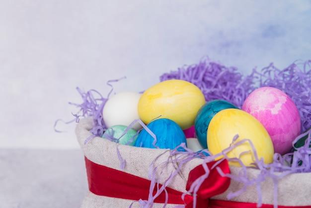 Conjunto de ovos de páscoa brilhantes na cesta decorada