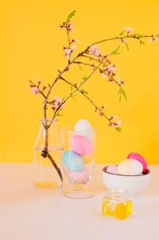 Conjunto de ovos de páscoa brilhantes perto de galho de flor em vaso com água e líquido de tintura