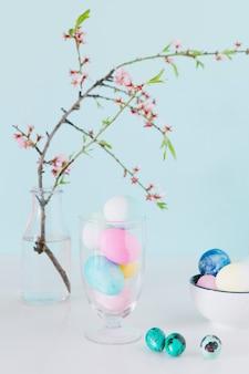 Conjunto de ovos de páscoa brilhantes perto de galho de flor em vaso com água e tigela