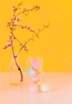 Conjunto de ovos de páscoa brilhantes perto de galho de flor em vaso com água