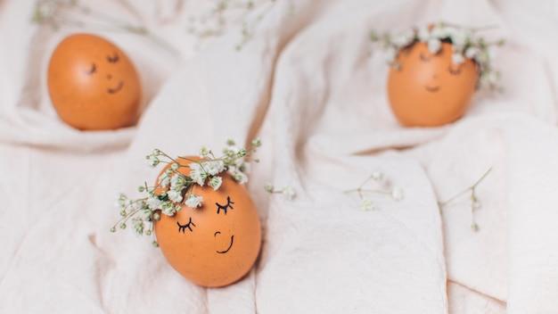Conjunto de ovos de páscoa com grinaldas de flores decorativas entre têxteis