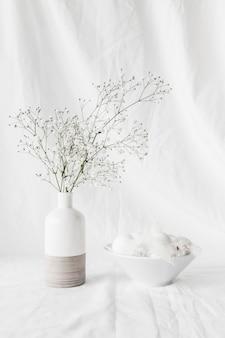 Conjunto de ovos de páscoa e penas na tigela perto de galhos de plantas em vaso