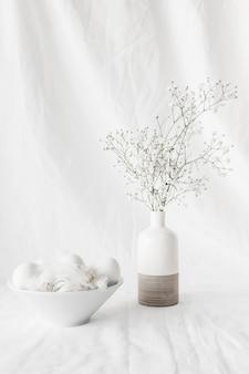 Conjunto de ovos de páscoa e penas na tigela perto de ramos de plantas em vaso