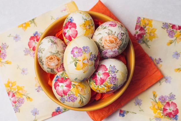 Conjunto de ovos de páscoa na tigela perto de guardanapos
