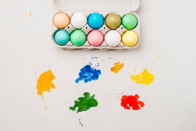 Conjunto de ovos de páscoa no recipiente perto de borrões de cores brilhantes