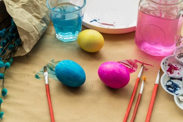 Conjunto de ovos de páscoa perto de copos de água, galhos de salgueiro e escovas