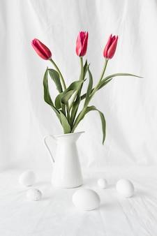 Conjunto de ovos de páscoa perto de flores em vaso