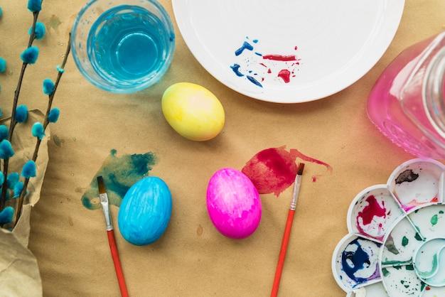 Conjunto de ovos de páscoa perto de galhos de salgueiro e escovas