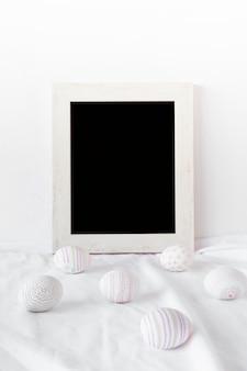 Conjunto de ovos de páscoa perto de molduras para fotos em têxteis