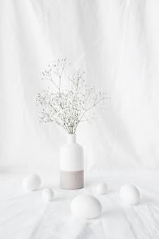 Conjunto de ovos de páscoa perto de ramos de plantas em vaso