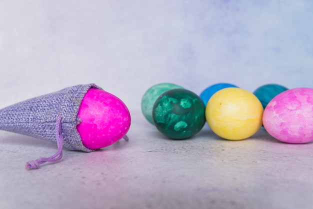 Conjunto de ovos de páscoa perto de saco ornamental