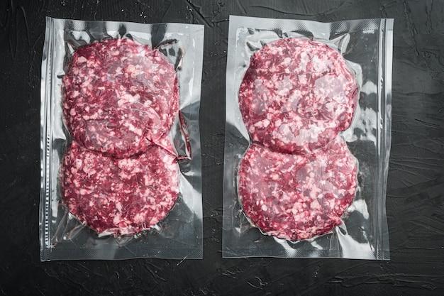 Conjunto de pacote hermético selado de costeleta de carne a vácuo, em mesa de pedra preta, vista de cima plano