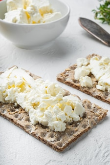 Conjunto de pães crocantes com manteiga, em mesa de pedra branca