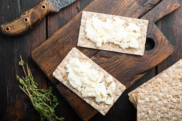 Conjunto de pães crocantes com manteiga, no antigo fundo da mesa de madeira escura, vista de cima plana