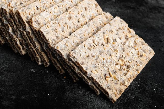 Conjunto de pães crocantes em mesa de pedra preta escura