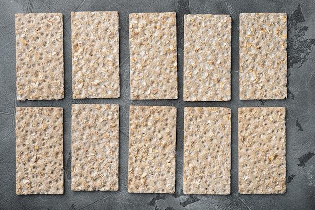Conjunto de pães crocantes, na mesa de pedra cinza, vista de cima plana
