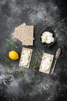 Conjunto de pães de centeio fresco com cream cheese, mesa de pedra preta escura, vista de cima plano