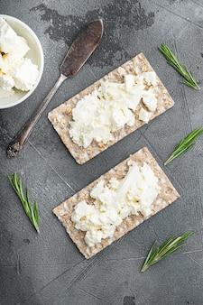 Conjunto de pães estaladiços com queijo feta, em mesa de pedra cinza