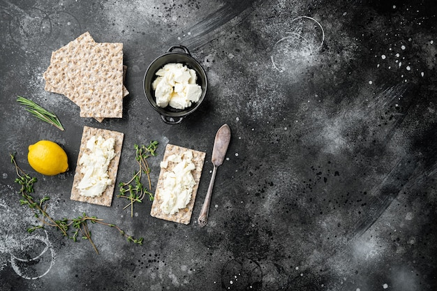Conjunto de pães estaladiços com queijo feta, em mesa de pedra preta escura, vista de cima plana lay