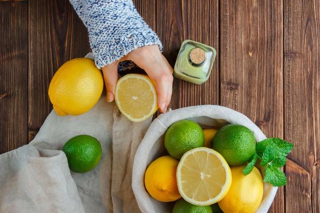 Conjunto de pano branco, mãos segurando limão e limões em uma cesta sobre uma superfície de madeira. vista do topo.