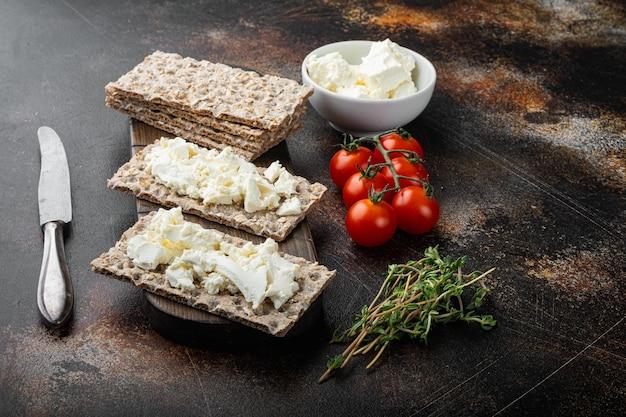 Conjunto de pão crocante de centeio integral com cream cheese, em fundo de mesa rústico escuro