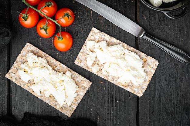 Conjunto de pão crocante de centeio integral com cream cheese, mesa de madeira preta, vista de cima plana lay