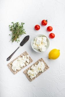 Conjunto de pão crocante de centeio integral com cream cheese, mesa de pedra branca, vista de cima plano