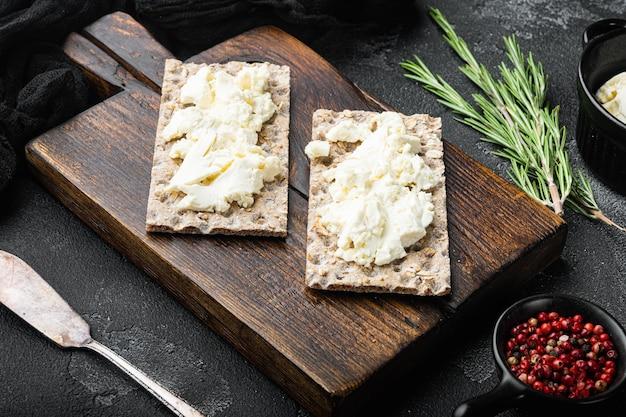 Conjunto de pão crocante de centeio integral com cream cheese, mesa de pedra preta escura