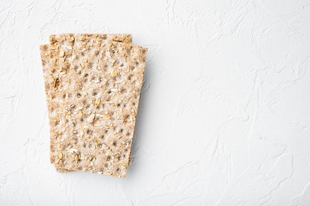 Conjunto de pão crocante de trigo mourisco, em mesa de pedra branca, vista de cima plana