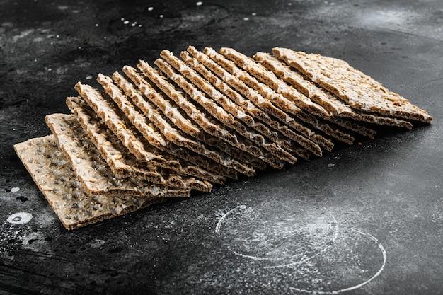 Conjunto de pão crocante de trigo sarraceno, em mesa de pedra preta escura