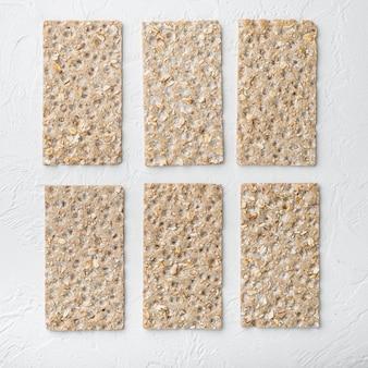 Conjunto de pão crocante leve dieta de grãos, formato quadrado, em mesa de pedra branca, vista de cima plano Foto Premium