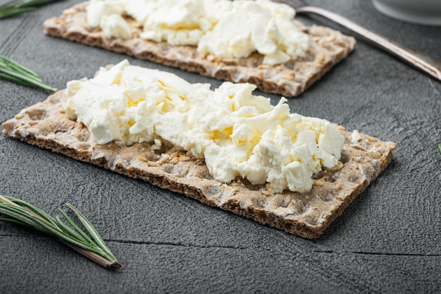 Conjunto de pão de centeio fresco com cream cheese, mesa de pedra cinza