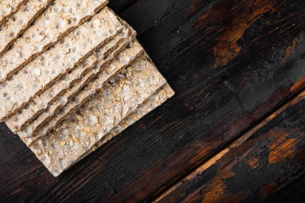 Conjunto de pão de lanche de baixas calorias, na velha mesa de madeira escura, vista de cima plana