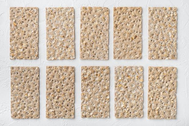 Conjunto de pão estaladiço com sementes de girassol, chia e gergelim, na mesa de pedra branca, vista de cima plana lay