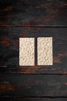 Conjunto de pão estaladiço com sementes de girassol, chia e gergelim, na velha mesa de madeira escura, vista de cima plana lay