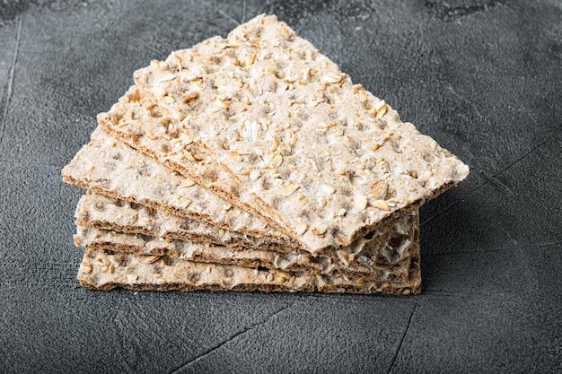Conjunto de pão estaladiço com sementes de girassol, chia e gergelim, no fundo da mesa de pedra cinza