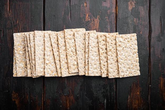 Conjunto de pão integral crocante, na velha mesa de madeira escura, vista de cima plana