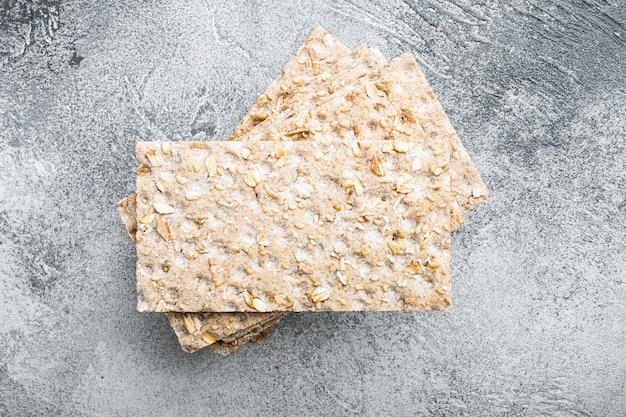 Conjunto de pão integral crocante, no fundo da mesa de pedra cinza, vista de cima plana