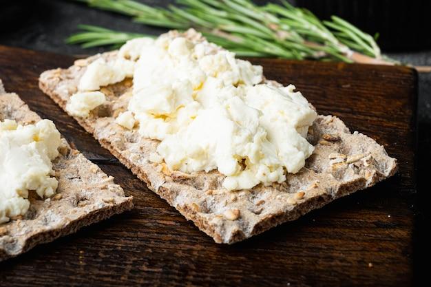 Conjunto de pão torrado com cream cheese, na mesa de pedra preta escura