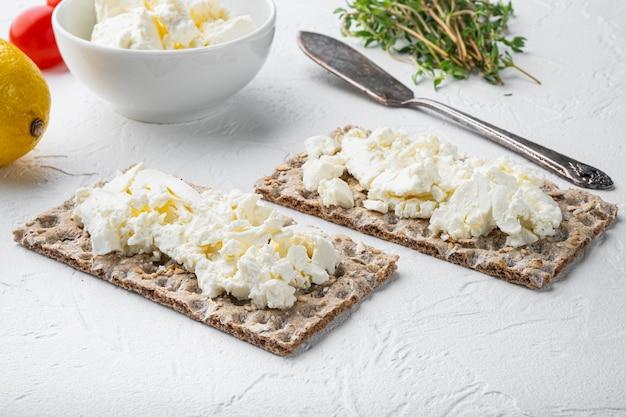 Conjunto de pão torrado com cream cheese, sobre mesa de pedra branca