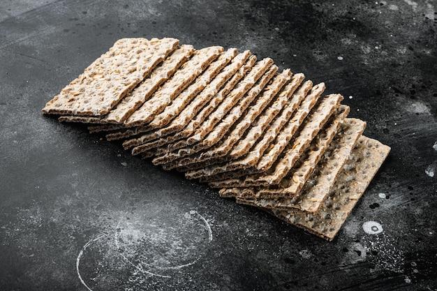 Conjunto de pão torrado com sementes de girassol, chia e gergelim, no fundo da mesa de pedra escura preta