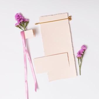 Conjunto de papéis perto de fita e flores