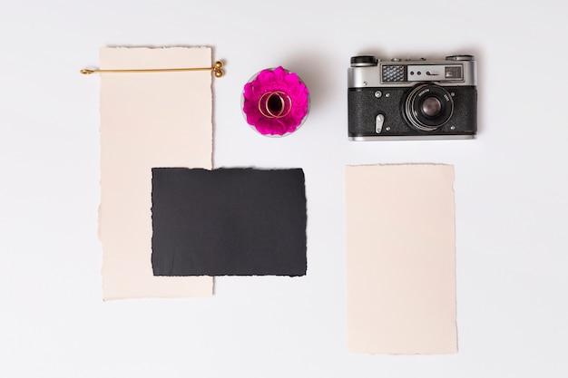 Conjunto de papéis perto de flores frescas com anéis na placa e câmera retro