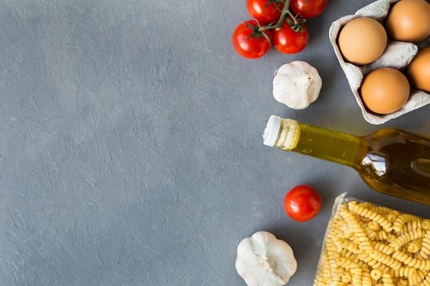 Conjunto de pedido online de produtos de massas, óleo, ovos, tomate da vista superior da loja em fundo cinza com espaço de cópia.