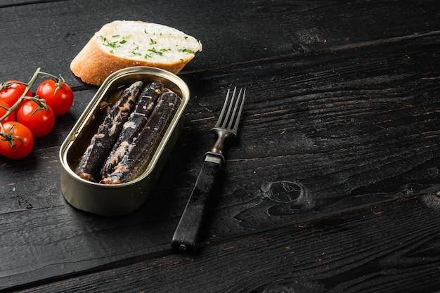 Conjunto de peixe em lata de ferro, no fundo preto da mesa de madeira, com espaço de cópia para o texto