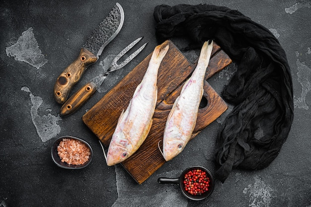 Conjunto de peixe inteiro fresco de cabra crua, com ingredientes e ervas, no fundo da mesa de pedra escura escura, vista de cima plana lay