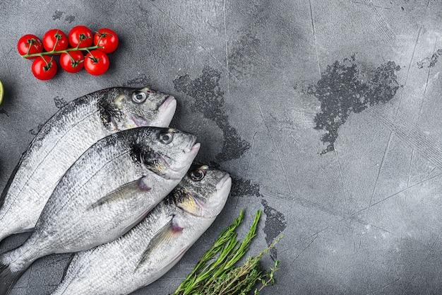 Conjunto de peixe orata dourada ou dourada dourada com ervas pimenta tomate limão para cozinhar e grelhar na mesa texturizada cinza, vista superior