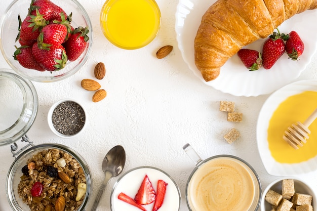 Conjunto de pequeno-almoço saudável: granola, bagas, croissant e café.