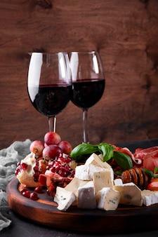 Conjunto de petiscos de vinho, jamon, calabresa, queijo, uva, pêssego e azeitonas na mesa.