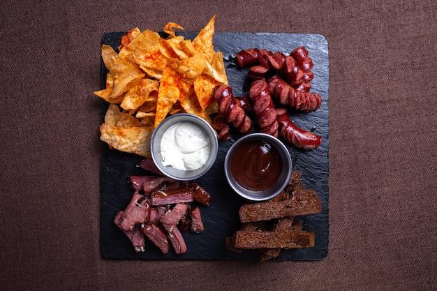 Conjunto de petiscos para cerveja no bar, conjunto de linguiça, carnes e biscoitos com vista de cima de batatinhas